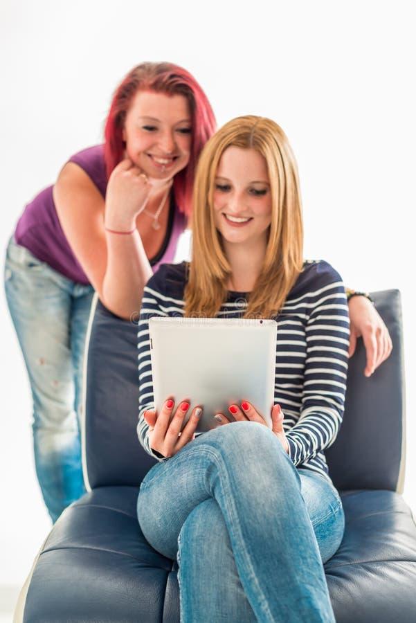 Twee jonge vrouwen die in jeans een tablet uitstellen royalty-vrije stock fotografie
