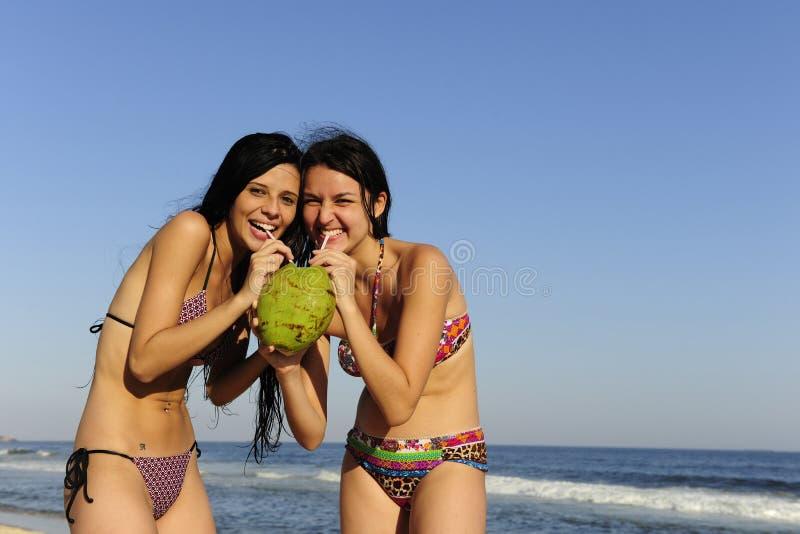 Twee jonge vrouwen die kokosnotenwater drinken stock afbeelding