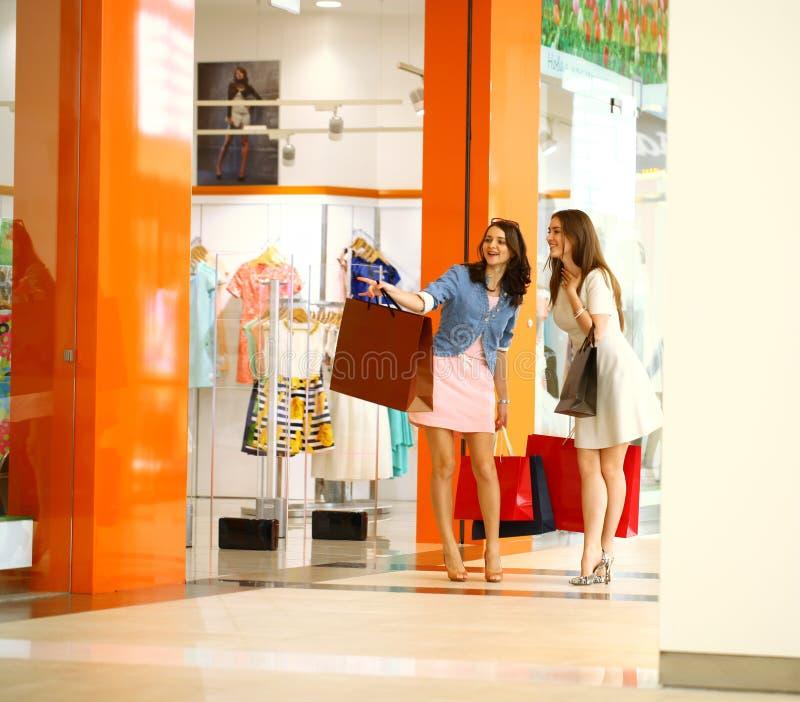 Twee jonge vrouwen die met het winkelen bij de opslag lopen stock afbeelding