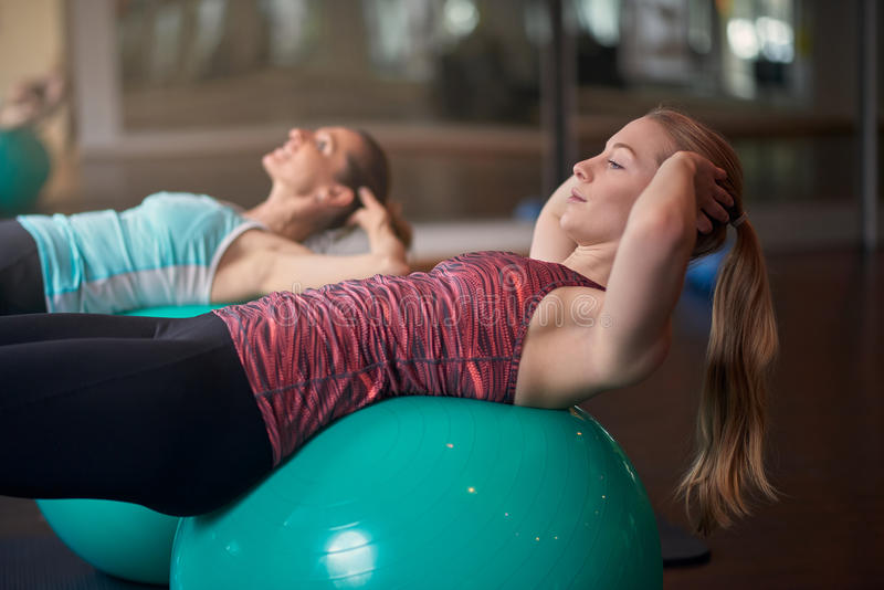 Twee jonge vrouwen die met pilatesballen uitoefenen royalty-vrije stock afbeeldingen