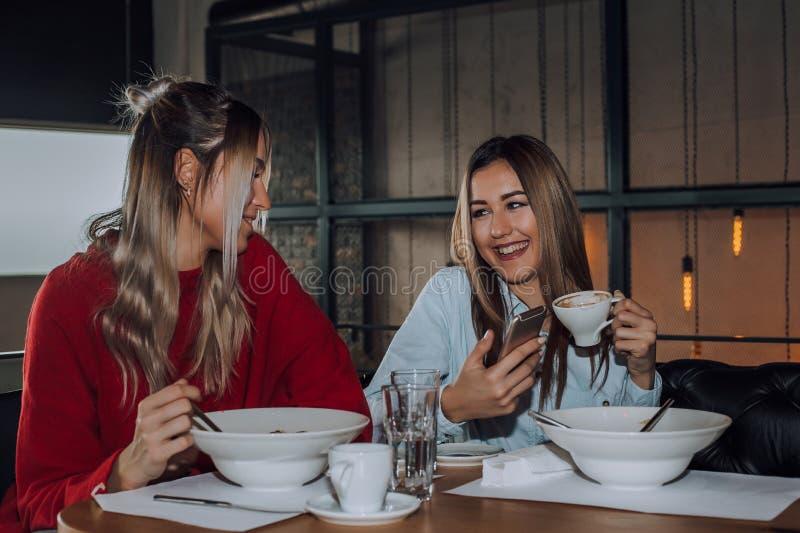 Twee jonge vrouwen die mobiele telefoon met behulp van terwijl het eten samen in een restaurant stock afbeelding