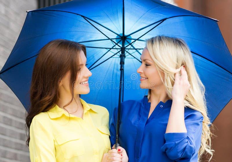 Twee jonge vrouwen die onder een paraplu stellen stock fotografie
