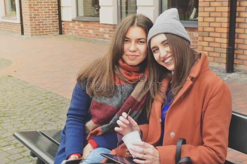 Twee jonge vrouwen die op de bank buiten zitten stock foto's