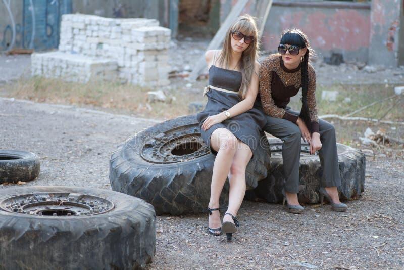 Twee jonge vrouwen die op grote banden in openlucht sitiing royalty-vrije stock foto's