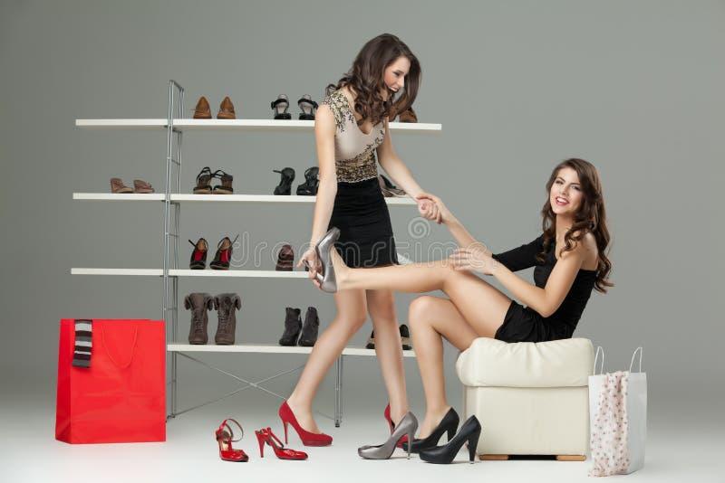 Twee jonge vrouwen die op hoge hielen proberen stock foto