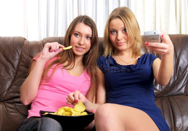Twee jonge vrouwen die op TV letten royalty-vrije stock afbeelding