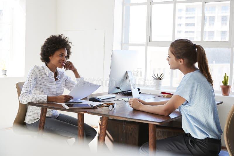 Twee jonge vrouwen die over hun bureaus in een bureau spreken royalty-vrije stock foto