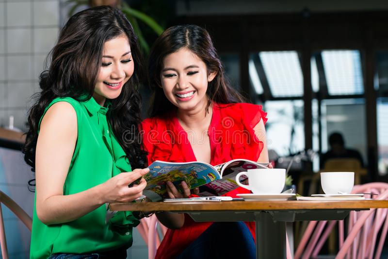 Twee jonge vrouwen die samen een in tijdschrift tijdens koffiepauze bekijken royalty-vrije stock afbeelding