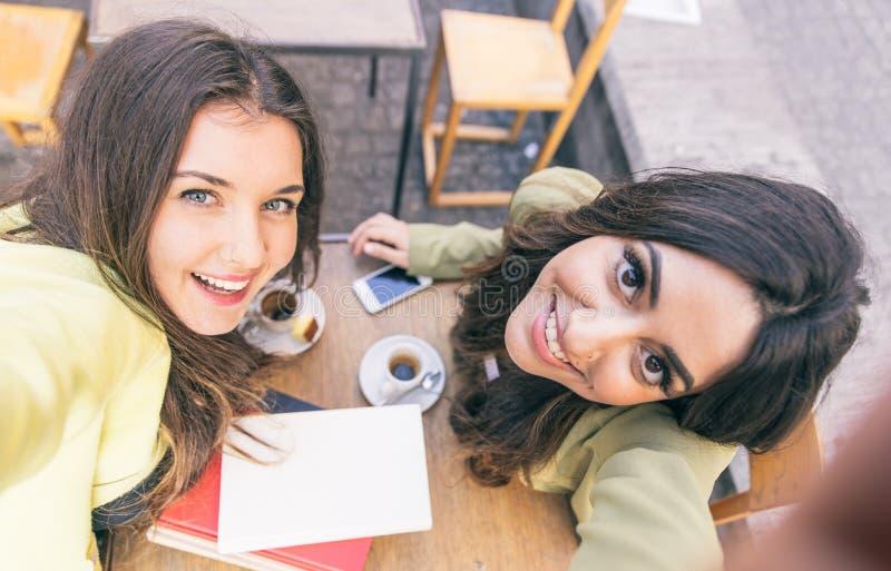 Twee jonge vrouwen die selfie met slimme telefoon nemen stock foto's