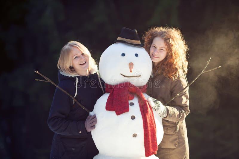 Twee jonge vrouwen die sneeuwman koesteren royalty-vrije stock afbeeldingen
