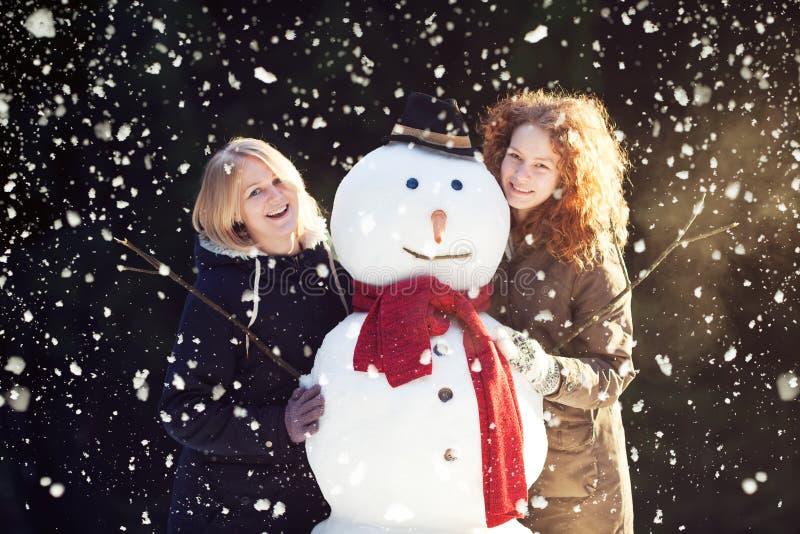 Twee jonge vrouwen die sneeuwman koesteren stock fotografie