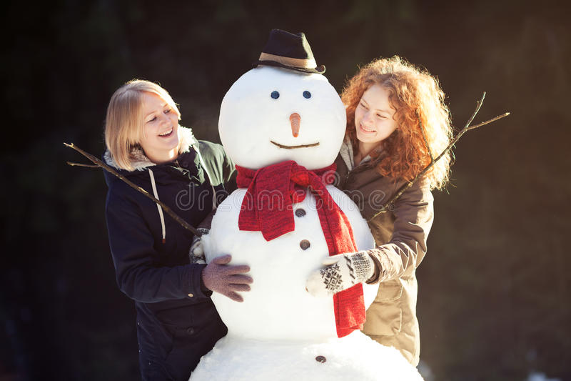 Twee jonge vrouwen die sneeuwman koesteren stock afbeelding