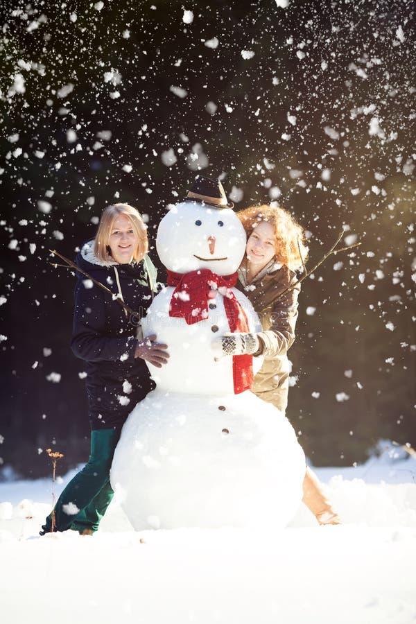 Twee jonge vrouwen die sneeuwman koesteren stock foto's