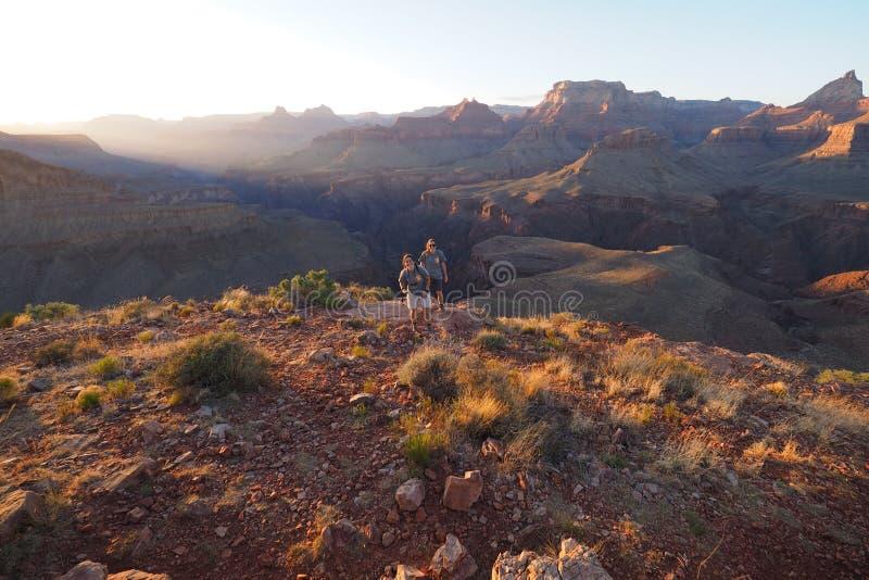 Twee jonge vrouwen die van de zonsondergang op Hoefijzermesa in Grand Canyon genieten stock afbeelding