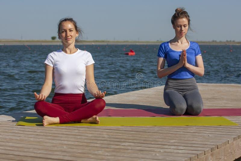 Twee jonge vrouwen die yoga doen bij aard Fitness, sport, yoga en gezond levensstijlconcept - groep die mensen yoga maken stellen stock foto