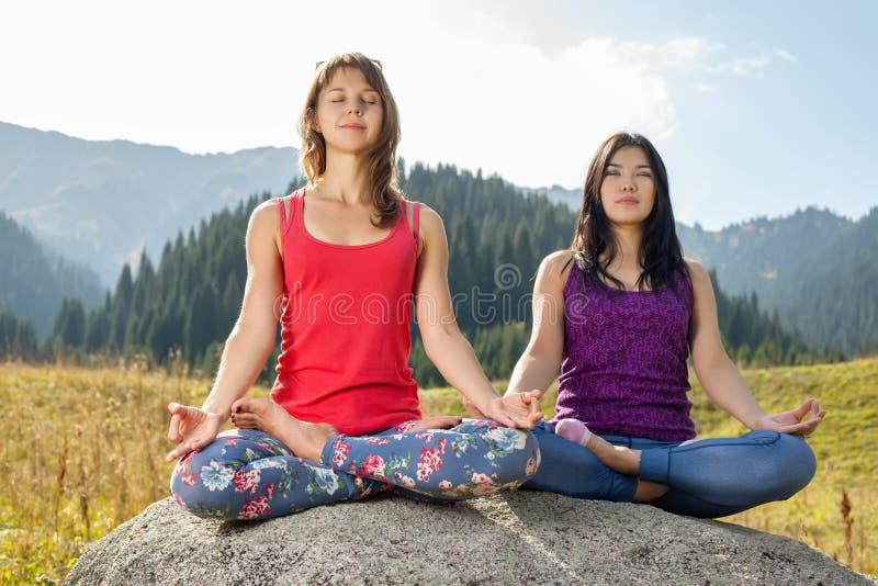 Twee jonge vrouwen die yoga op een rots doen stock foto