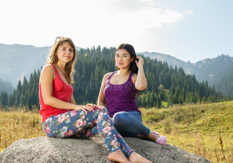 Twee jonge vrouwen die yoga op een rots doen royalty-vrije stock foto's