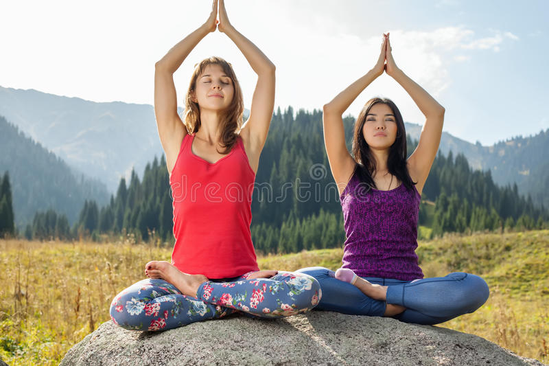 Twee jonge vrouwen die yoga op een rots doen stock afbeelding