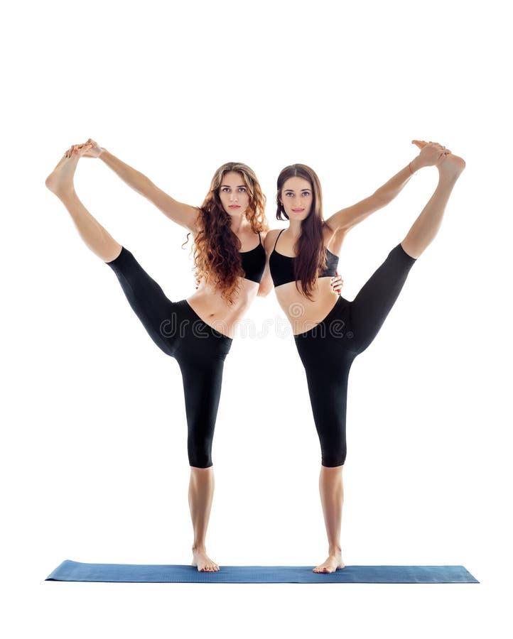 Twee jonge vrouwen die yogaasana uitgebreide hand doen aan grote teen stellen royalty-vrije stock afbeeldingen