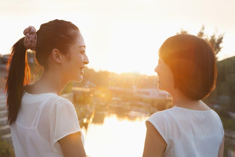 Twee Jonge Vrouwen die Zonsondergang bekijken royalty-vrije stock afbeelding