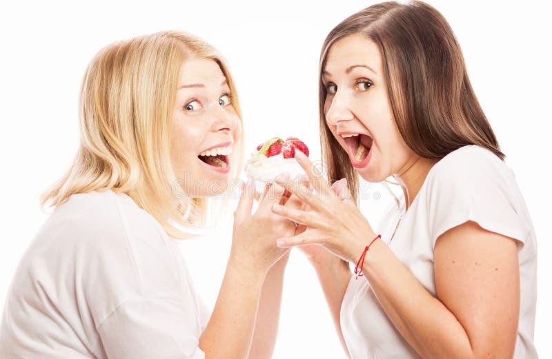 Twee jonge vrouwen eten een cake stock afbeelding