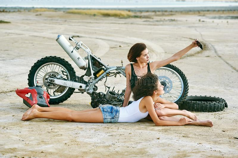 Twee jonge vrouwen hebben pret het spelen op een gedemonteerde motorfiets stock afbeelding