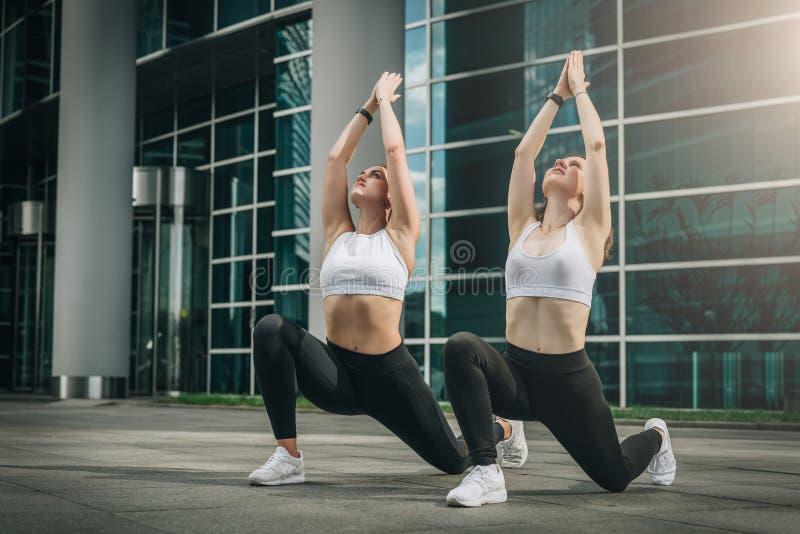 Twee jonge vrouwen, meisjes die uitrekkende oefeningen, opwarming doen, die yoga op stadsstraat doen Training, die op stadsstraat royalty-vrije stock foto