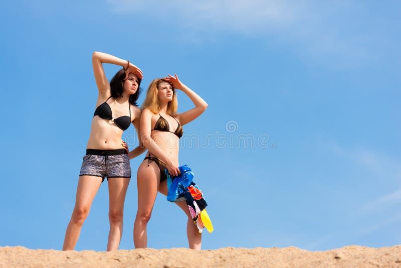 Twee jonge vrouwen met blauwe hemel in de zomer royalty-vrije stock afbeelding