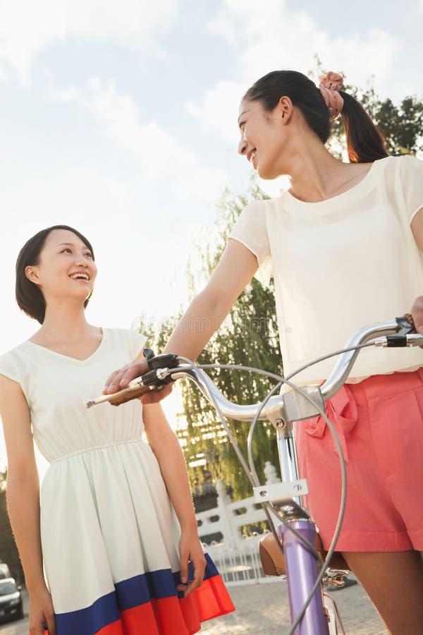 Twee Jonge Vrouwen met Fiets royalty-vrije stock afbeelding