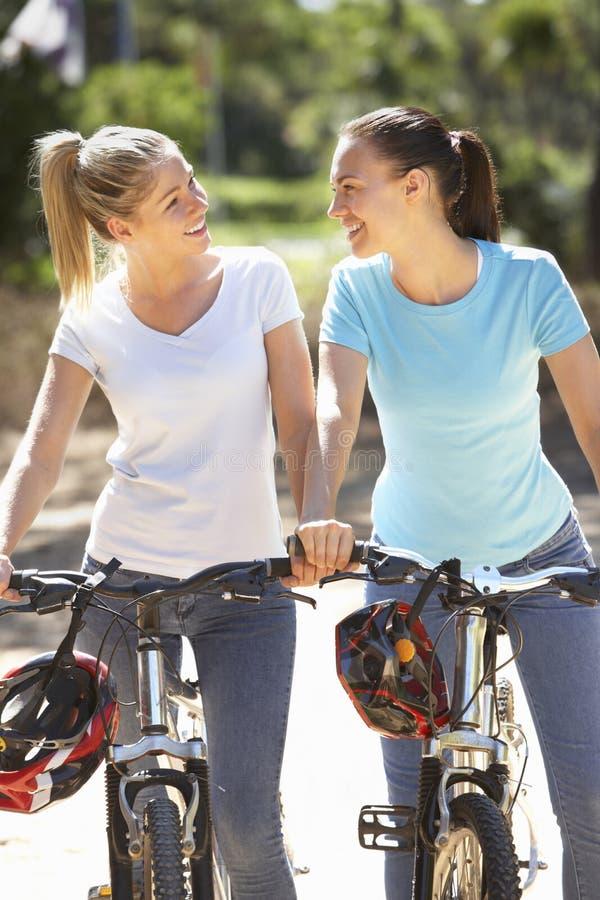 Twee Jonge Vrouwen op Cyclusrit samen royalty-vrije stock afbeeldingen