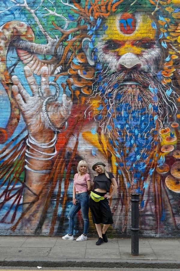 Twee jonge vrouwen stelt onder geschilderde yogi stock afbeelding