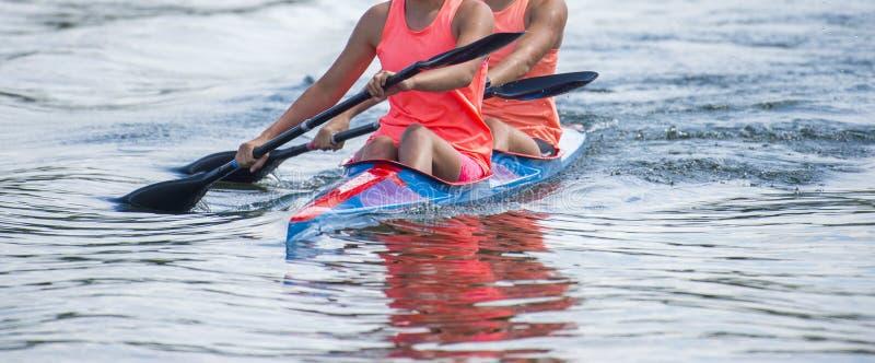 Twee jonge vrouwenatleten bij het roeien van kajak op meer tijdens de concurrentie stock foto