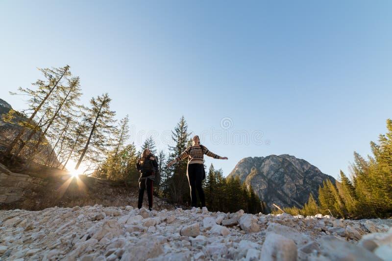 Twee jonge vrouwentoerist die op de rots op een achtergrond van bergen lopen royalty-vrije stock afbeeldingen