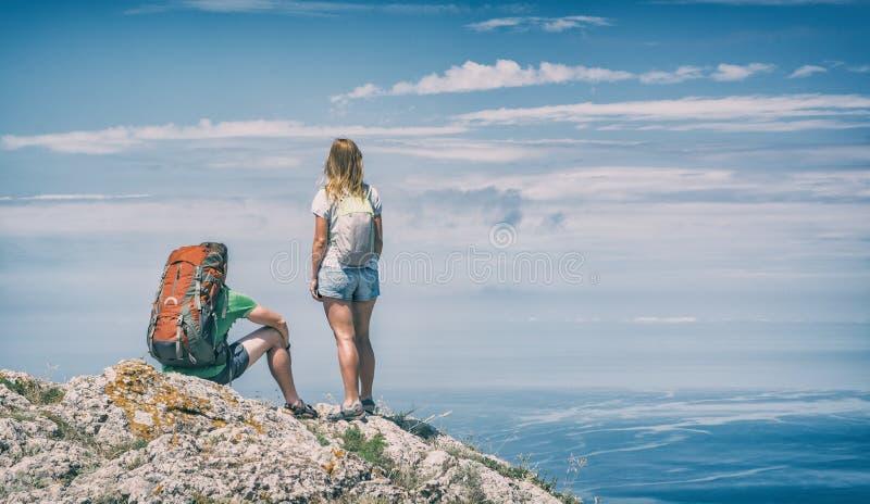 Twee jonge wandelaars boven het overzees stock fotografie