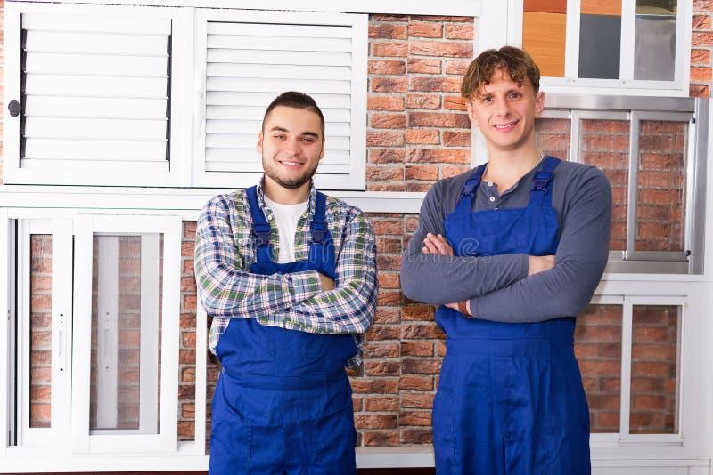 Twee jonge werklieden die vensters inspecteren stock afbeeldingen