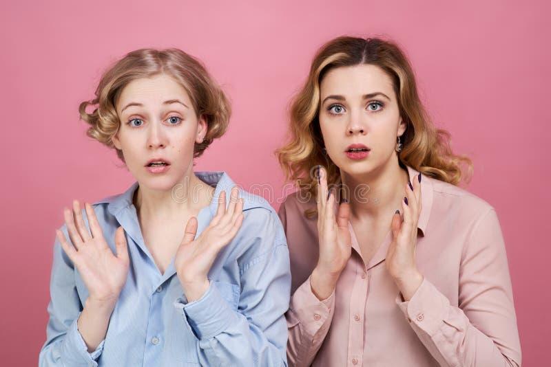 Twee jonge wit-gevilde meisjes worden overweldigd door het incident en het openen van hun monden met hun handen royalty-vrije stock afbeelding