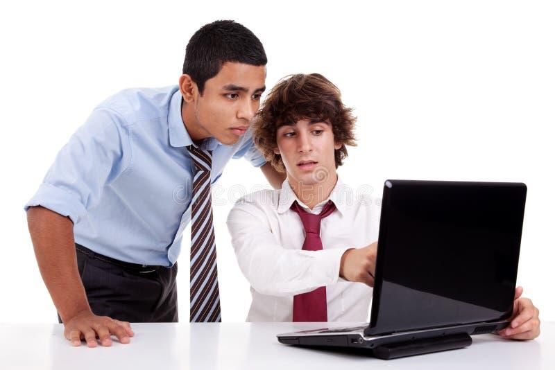 Twee jonge zakenlieden die aan laptop samenwerken