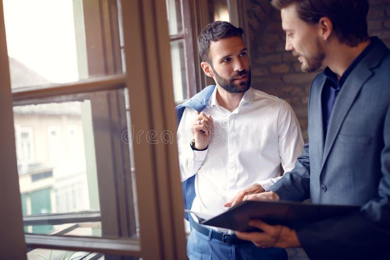 Twee jonge zakenlieden die in bureau spreken stock afbeeldingen