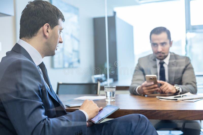 Twee jonge zakenlieden die elektronische apparaten met behulp van op commerci?le vergadering royalty-vrije stock afbeelding