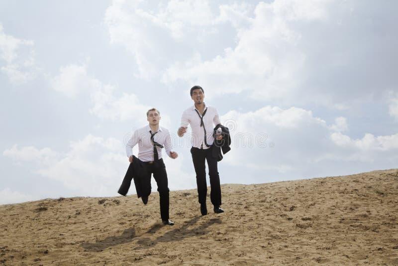 Twee jonge zakenlieden die en uitgeput in de woestijn lopen, die jasjes houden stock afbeelding