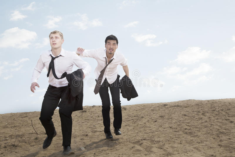 Twee jonge zakenlieden die en uitgeput in de woestijn lopen, die jasjes houden stock fotografie