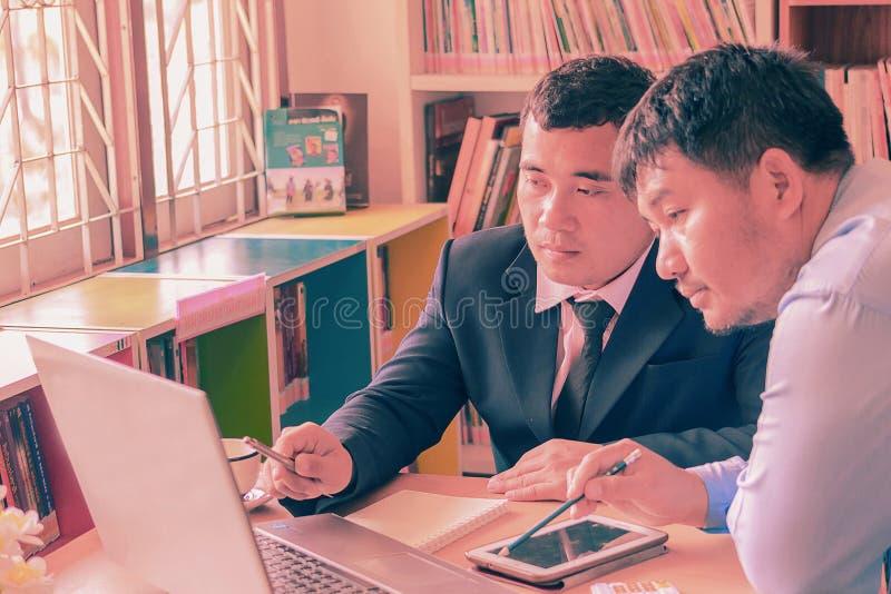Twee jonge zakenlieden die op vergadering in bureau op elkaar inwerken, royalty-vrije stock fotografie