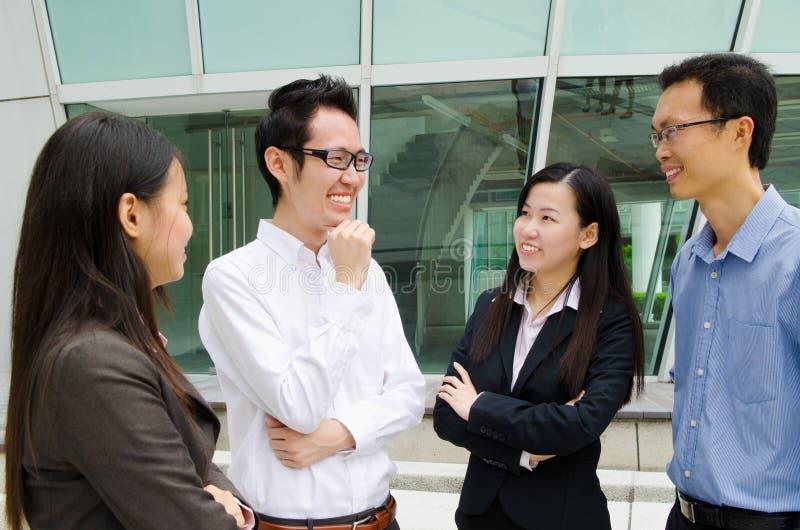 Twee jonge zakenlieden die over zaken spreken terwijl één van hen die op de computer leunen controleert royalty-vrije stock fotografie