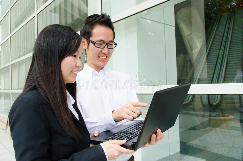 Twee jonge zakenlieden die over zaken spreken terwijl één van hen die op de computer leunen controleert royalty-vrije stock afbeeldingen