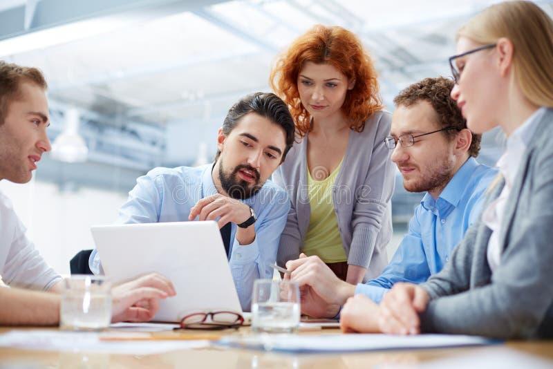 Twee jonge zakenlieden die over zaken spreken terwijl één van hen die op de computer leunen controleert stock foto
