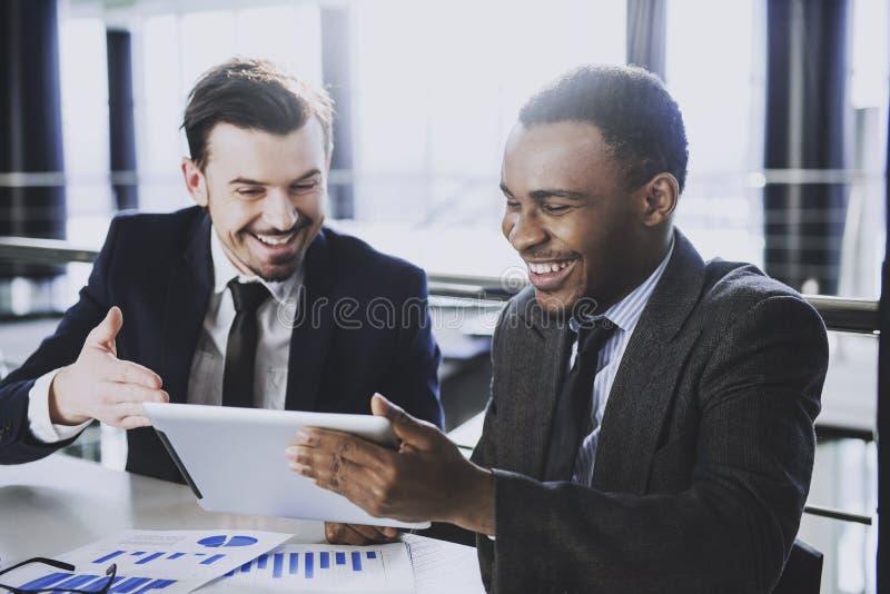 Twee jonge zakenlieden werken met PC-tablet in modern bureau stock foto