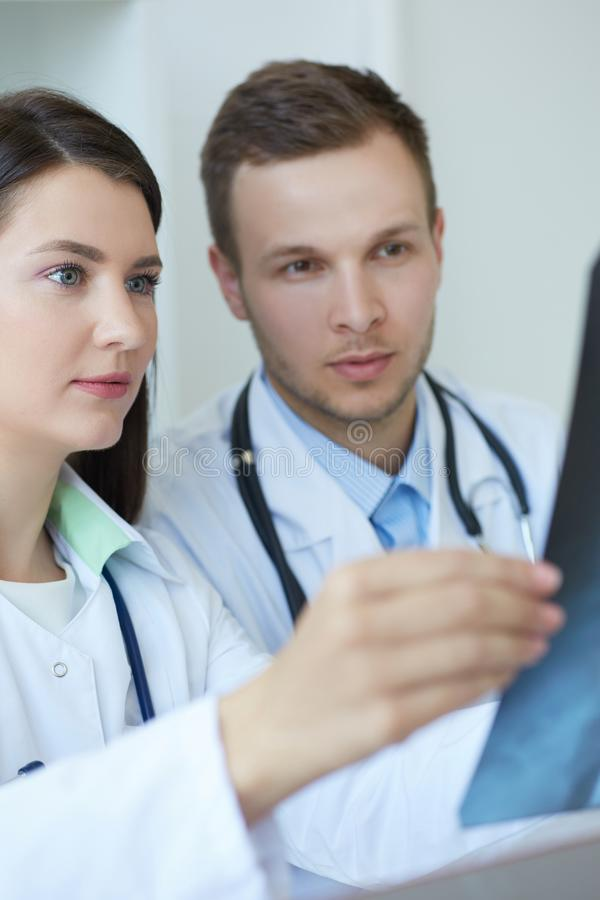 Twee jonge zekere artsen die de röntgenstraal van hun patiënt controleren en een diagnose maken Radioloog of traumatologist stock foto