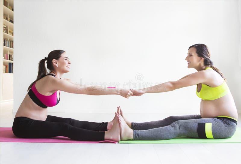 Twee jonge zwangere vrouwen die geschiktheidsoefeningen doen stock afbeeldingen