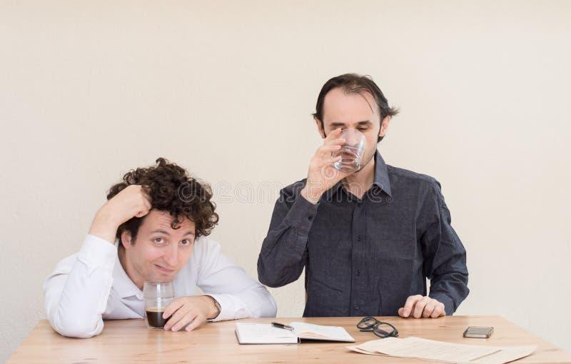 Twee jongelui bored Kaukasische collega's die bij de lijst in het bureau met lichte achtergrond zitten royalty-vrije stock afbeeldingen