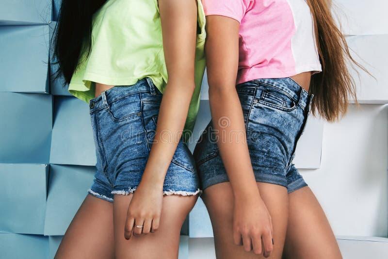 Twee jongelui past meisjes in de hoge borrels van taillejeans en heldere mede stock foto's